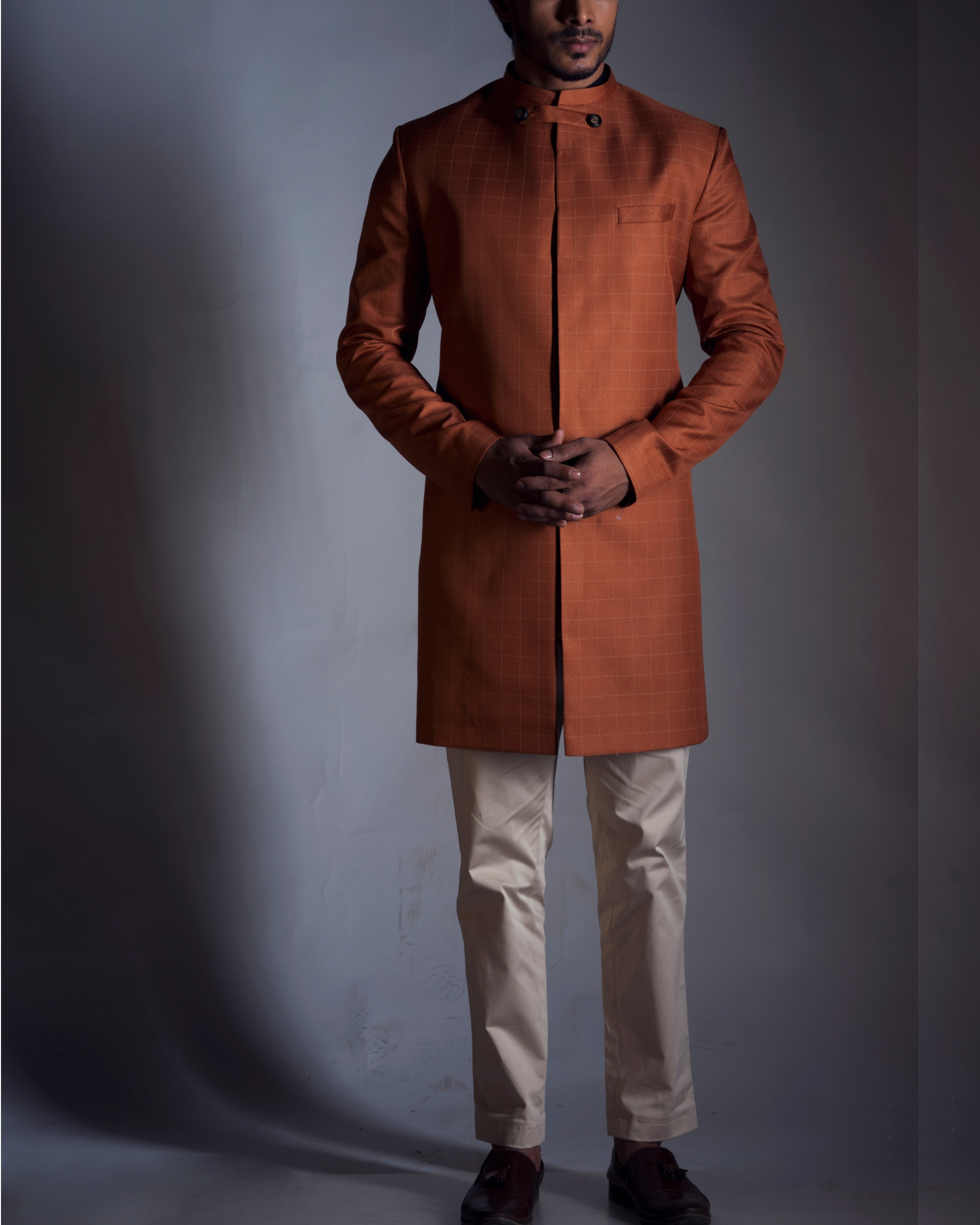 Rust orange achkan with cream trousers