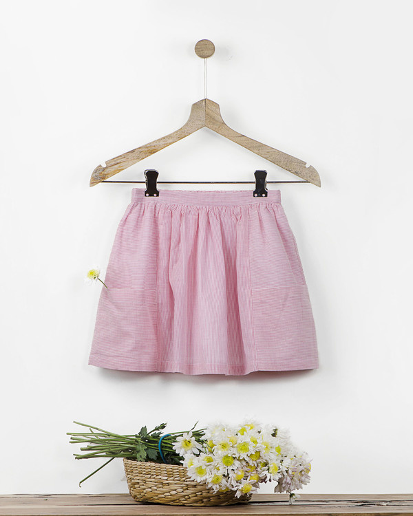 Pink and white pinstriped skirt with fabric brooch